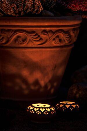 Candle lanterns beside terracotta flowerpot in the garden