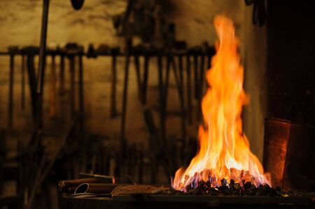Close-up of traditional blacksmith's forge, hot flames and coal