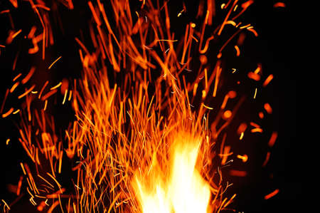Close-up of sparks and flames against black bakground.