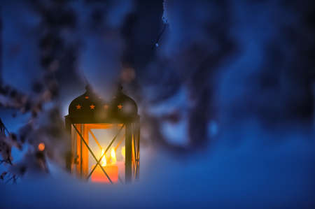 Candle lantern in snow at dusk