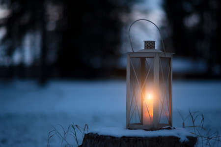 Candle lantern in snow against defocused forest background. Stockfoto