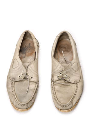 A pair of old walking shoes on white background.