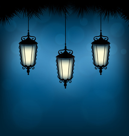 pine three: Three illuminated lanterns with pine branches on blue background Stock Photo