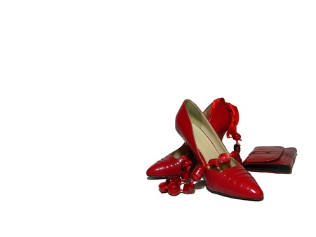 female pair of red shoes and red beadsand red purse                              Stock Photo
