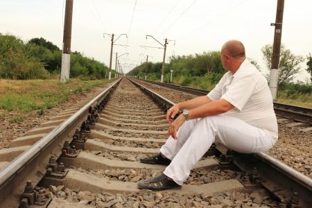 Thoughtful man sitting on railroad tracks