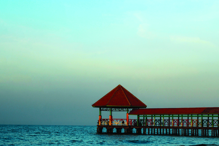 Pier on Purin beach, Tegal Regency, Indonesia with medium waves