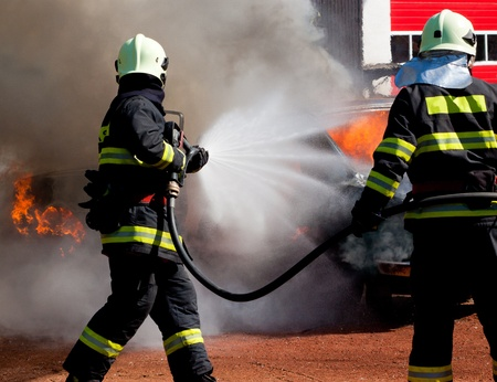 The firemans are extinguish a exploded burning car Stock Photo - 13417326