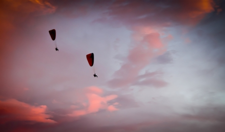 Silhouette of powered paraglide against sunset sky