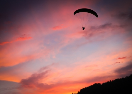 Silhouette of powered paraglide against sunset sky Stock Photo - 15491869