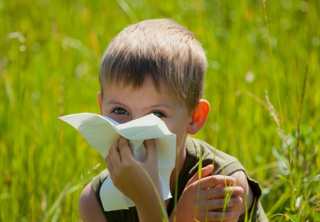 Little boy is blowing his nose on green meadow