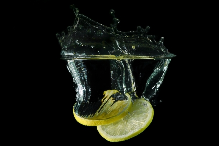 sliced lemon dropped under water