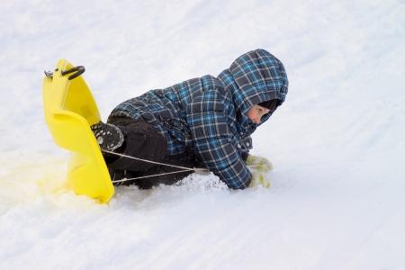 overturn: Ragazzino sulla slitta - facendo un incidente ribaltare Archivio Fotografico
