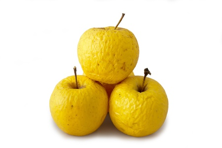 Three very old golden apples over white background