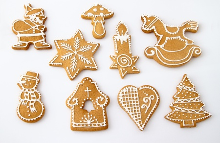 Homemade Christmas Ginger and Honey cookies on white background. Star, fir tree, snowflake, horse, bell, mushroom, Santa Claus, snowman, rocking horse, candle, heart - shapes.