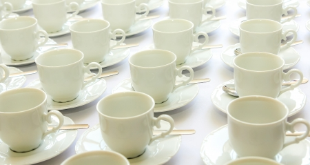 Stacked coffee cups with saucers and spoons ready for use Stock Photo