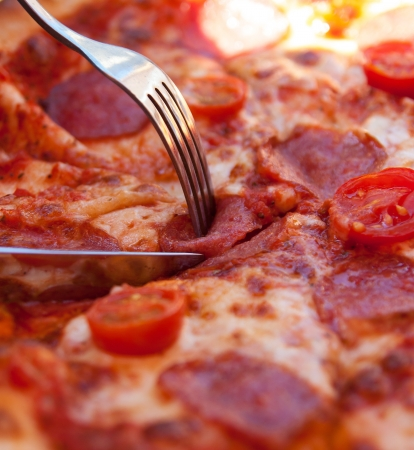Cutting a delicious Italian pizza with salami, cheese and tomatoes with help of knife and fork Stock Photo - 22146606