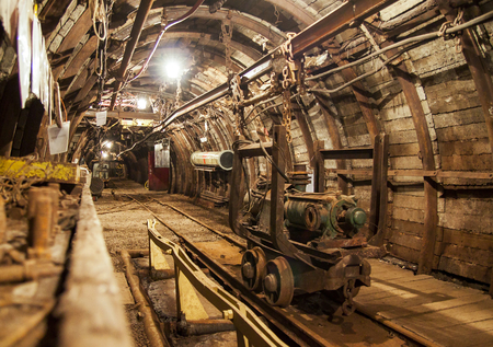 Interior of underground mine passage with rails, light and carriage - mining industry photo