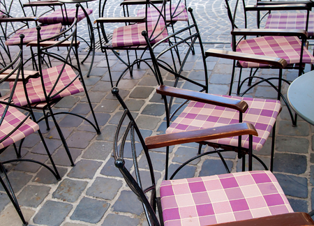 Empty tables and metal chairs in a cafe and restaurant on the street on grey paving