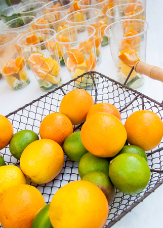 Citrus fruits in basket ready to make juice with glasses in the background Stock Photo
