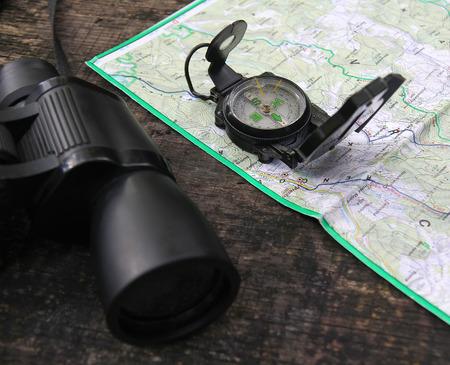 puntos cardinales: Binoculares y una brújula en el mapa en el medio natural durante el senderismo
