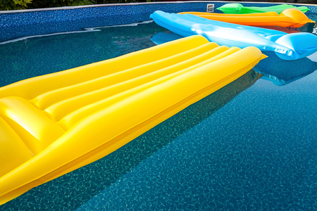 Multicolored air mattresses floating on the calm surface of a smaller pool in the garden of a house without people
