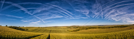 Wavy fairytale spring landscape with fields and contrails (chemtrails) on the sky Moravian Fields - an area called the Moravian Tuscany, Czech republic, Europe