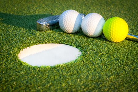 Close up image of golf hole with balls and putt Stock Photo