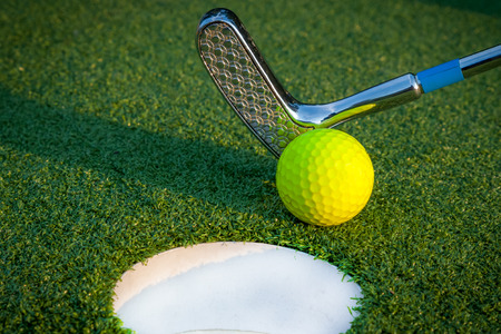 Close up image of golf hole with yellow ball and putt Banco de Imagens