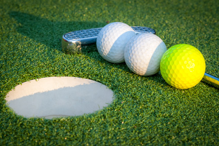 Close up image of golf hole with balls and putt Banco de Imagens