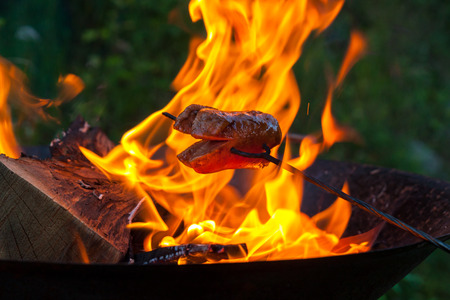 Close-up picture of roasting the sausages on the camp fire