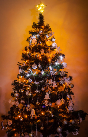 Beautifully romantic decorated Christmas tree with Multi Colored Lights on warm background. Christmas concept.