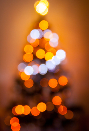 Defocused blurry christmas tree silhouette with blurred lights on warm background. Christmas concept.