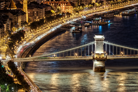 Danube river with traffic on river bank and illuminated Chain bridge in Budapest at night. View from Gellert Hill. Hungary, Europe. Stock Photo