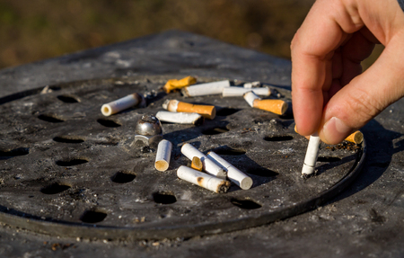 Close up picture of dirty street ashtray with a hand extinguishing cigarette at smoking area. Hand putting out a cigarette. Imagens