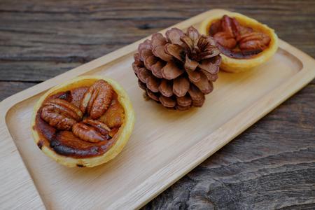 mini oven: Pumpkin Pecan tart and pine cone on wooden board Stock Photo