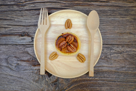 mini oven: Pumpkin Pecan tart and pine cone on wooden plate with fork and spoon Stock Photo