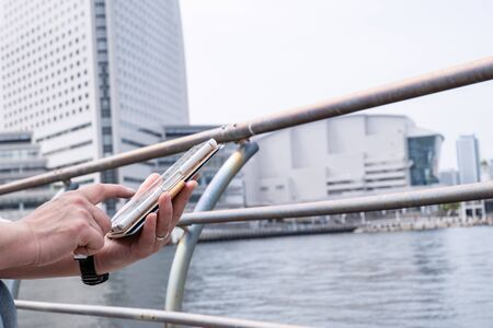 Woman's hand to operate the smartphone at Shinko Park