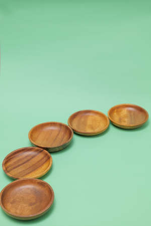 a round wooden dish placed on a green background