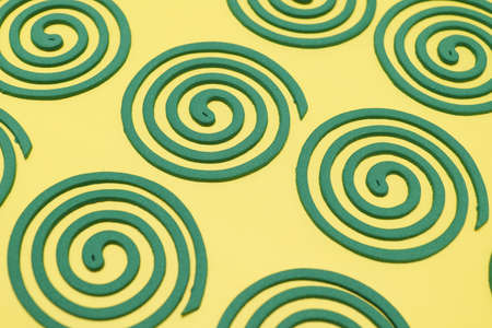 a spiral mosquito coil placed on a yellow background Фото со стока
