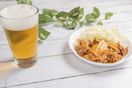 Cold beer and pork kimchi placed on a table with light 写真素材
