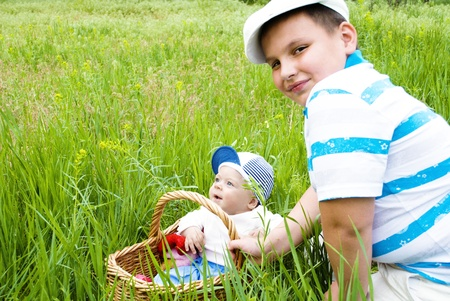 Baby in a basket, surrounded by grass and flowers photo