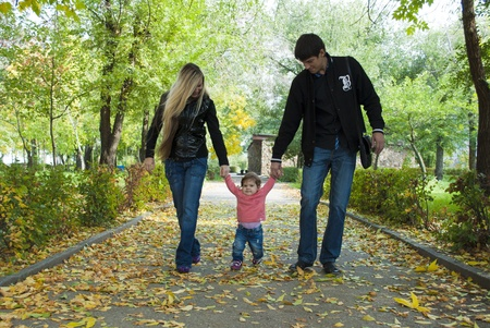 Family walk in the park with fun toys, the bright sun illuminates the faces of children and parents, and rustling leaves underfoot on the grass Stock Photo - 10836305