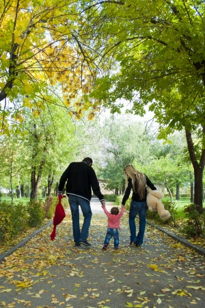 Family walk in the park with fun toys, the bright sun illuminates the faces of children and parents, and rustling leaves underfoot on the grass