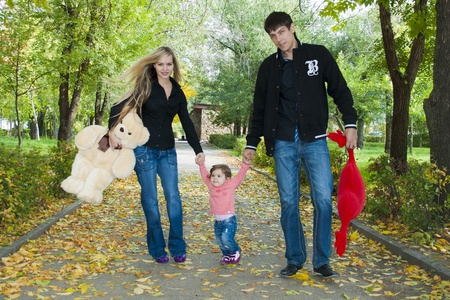 Family walk in the park with fun toys, the bright sun illuminates the faces of children and parents, and rustling leaves underfoot on the grass photo