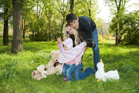 Family walk in the park with fun toys, the bright sun illuminates the faces of children and parents, and rustling leaves underfoot on the grass Stock Photo - 10836309