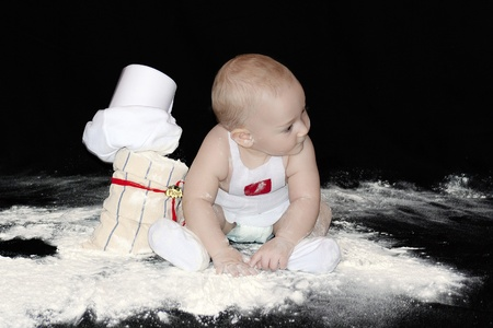 A little boy in an apron, busy in the sack of flour on the black background  photo