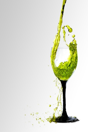 purify: Colored liquid poured into a clear glass with black stem and spills over the edge.