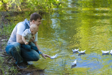 Little boy at the hands of parents let a paper boat in the water of Lake Forest. photo