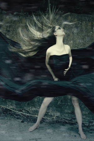 Beautiful girl witch, in a dense forest at the foot of the rocks involved in witchcraft  photo