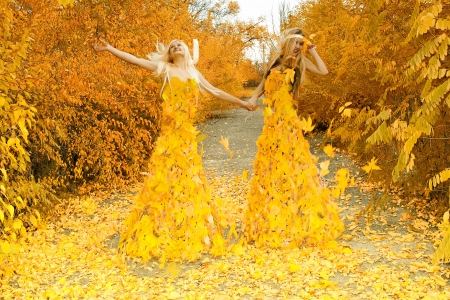 Two girls, in dresses from leaves, having joined hands, walk on a footpath in autumn wood photo